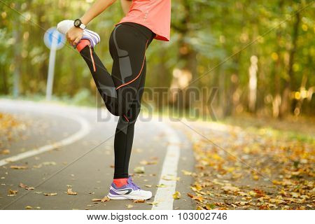 Detail of woman stretching legs before jogging in autumn nature
