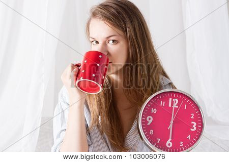 Happy girl  wake up with alarm clock and  coffee cup 6 a.m