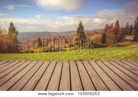 Wooden planks floor with autumn mountain landscape in the background.