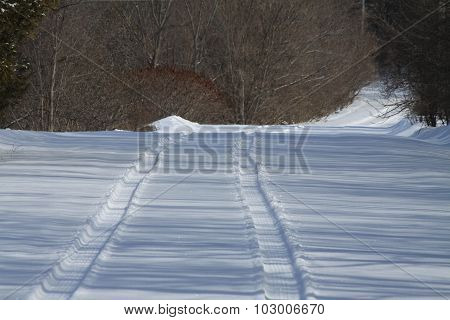 Tire Tracks in Snow on Roadway