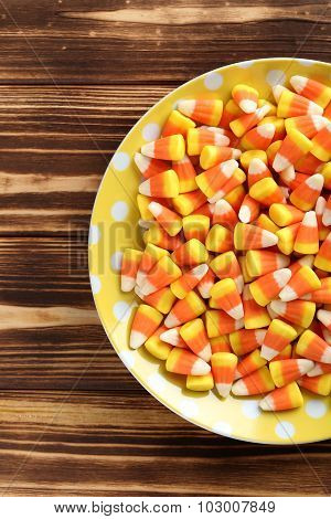 Halloween Candy Corns In Plate On Brown Wooden Background