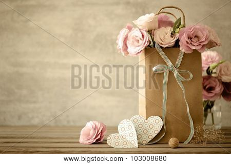 Love background with pink flowers, bow and paper handmade hearts, vintage toned