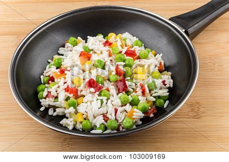 Frying Pan With Vegetable Mix On Board