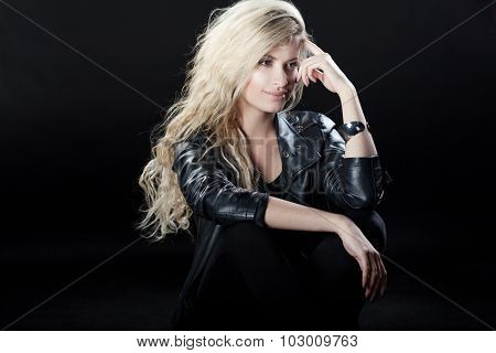 Beautiful and stylish young blonde girl, black background