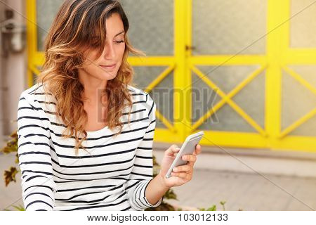 Young Woman Using Smart Phone While Sitting