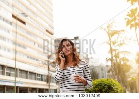 Young Woman Speaking On Cell Phone While Walking
