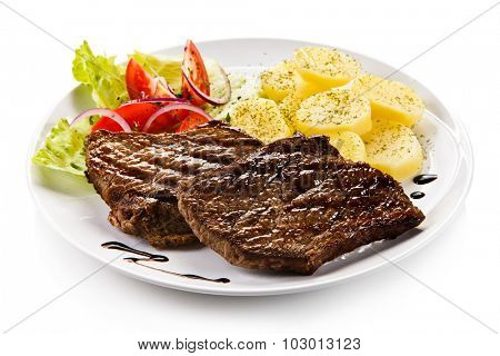 Grilled steaks, boiled potatoes and vegetable salad