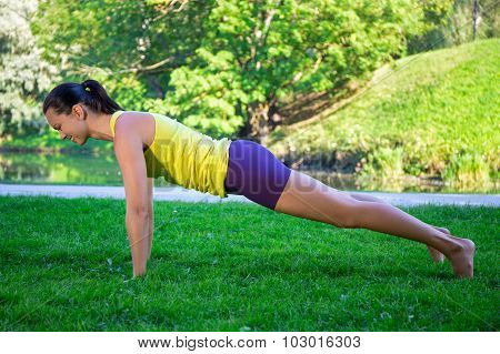 Beautiful Sporty Woman Doing Push Up Exercise In Park