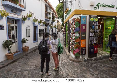 Two Young Girls Take Photo In The Romero Street, Jewish Quarter In Cordoba, Province Cordoba, Andalu