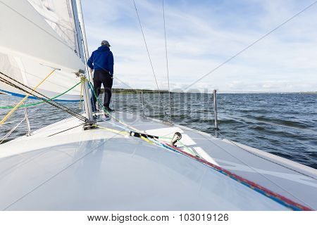 Man Standing On Front Part Of Yacht Swim By Lake
