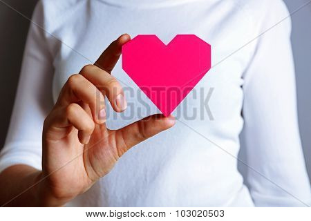 Closeup of plastic puzzle heart in female hand
