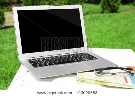Laptop and newspaper on wooden table outdoors