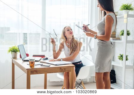 Two young woman colleague at office working standing and talking