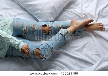 Woman in blue jeans on bed top view