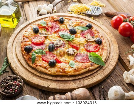 Pizza with mushrooms, salami and tomatoes. Top view.