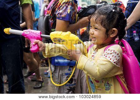 Little Asian Girl Shooting Water Gun At Songkran Festival In Bangkok, Thailand