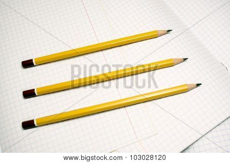 Pencils on a checkered (squared) notebook background