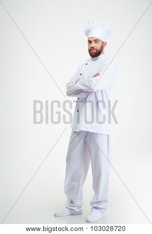 Full length portrait of a happy male chef cook standing with crossed hands isolated on a white background