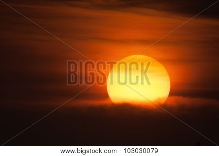 Close up image of Sun setting behind the cloud