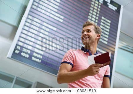 Smiling man at board at the airport