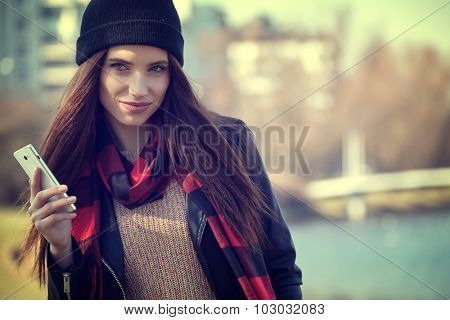 Young beautiful autumn woman with cell phone