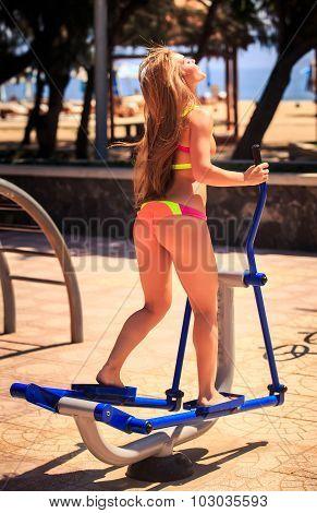 Backside Blonde Girl In Bikini Trains On Stepper On Sport Ground