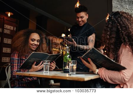 Young Girls At Cafe Giving Order To The Waiter