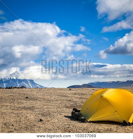 Camping tent on a rocky campsite in Iceland with stones keeping tent grounded
