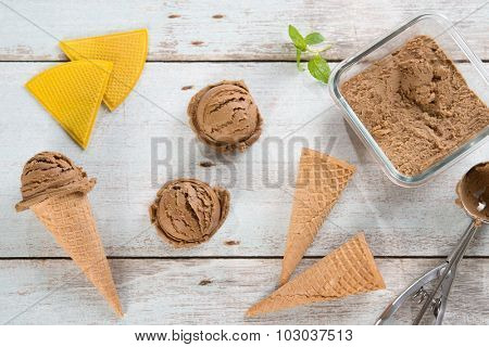 Top view brown ice cream in waffle cone with utensil on rustic wooden background.