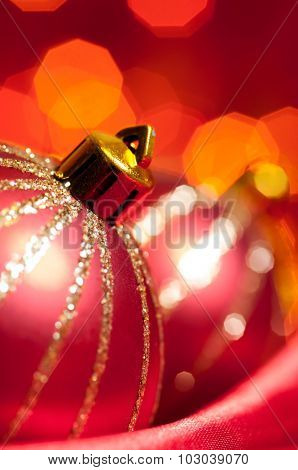 christmas decorative balls on red silk against blurred lights on background