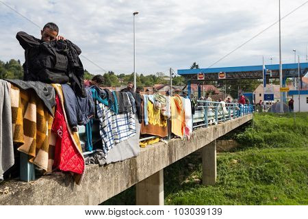 HARMICA, CROATIA: SEPTEMBER20, 2015: Immigrants and refugees from Middle East and North Africa drying blankets and clothes at bridge fence at Harmica, state border between Slovenia and Croatia.