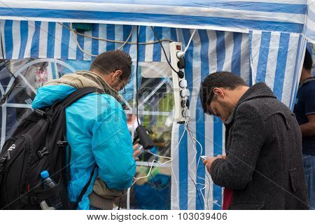 BREGANA, SLOVENIA: SEPTEMBER 19, 2015: Immigrants and refugees from Middle East and North Africa at Bregana, state border between Slovenia and Croatia. Two men charging their cell phones.