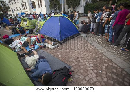 KOS, GREECE - SEP 28, 2015: Unidentified war refugees near tents. More than half are migrants from Syria, but there are refugees from other countries -Afghanistan, Pakistan, Iraq, Iran, Mali, Somalia.