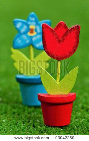 Nice artificial flower in small flowerpot on artificial green grass