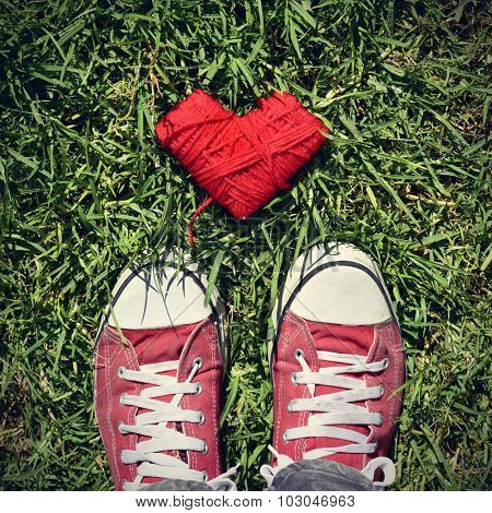 a heart-shaped coil of red rope and the feet of a man wearing red sneakers stepping on the grass, with a slight vignette added