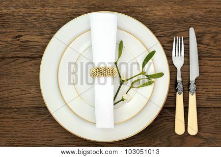 Christmas dinner table setting with plates, cutlery, napkin and  mistletoe over old oak table background.