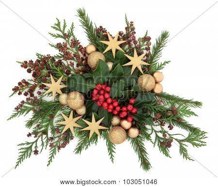 Christmas flora with gold bauble and star decorations with holly, ivy and winter greenery over white background.