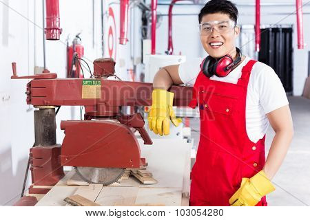 Proud Chinese carpenter in his wood workshop standing next to an electrical circular saw