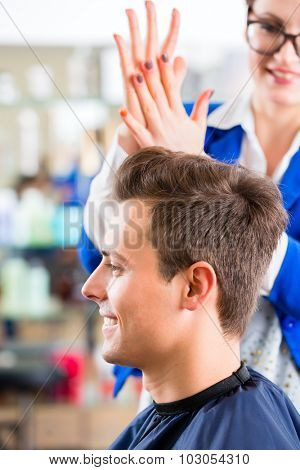 Female coiffeur cutting men hair in hairdresser shop