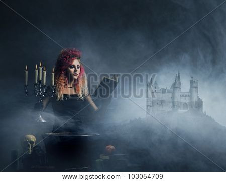 Witch conjuring over the smoky background with a castle on a mountain. Halloween concept.