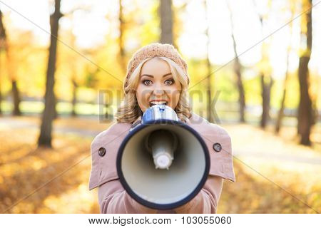 Beauitiful woman speaking to amplifier in the autumn park.