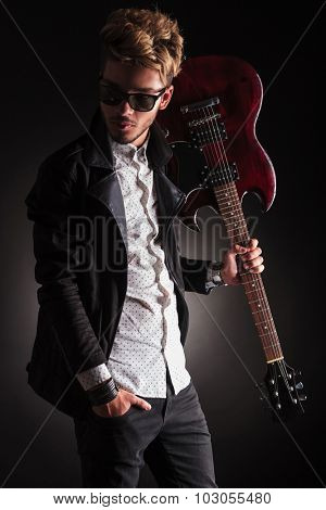 side view of a young rocker holding his guitar on shoulder and looking back on black studio background