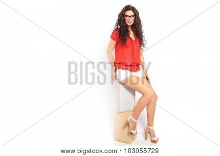 smart girl with curly hair wearing glasses, sitting on a chair and touching her leg while looking at the camera