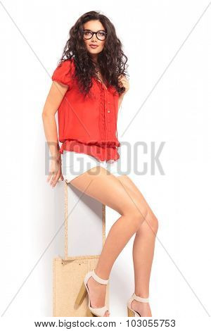cute girl sitting on a chair and fixing her hair while posing and looking away from the camera