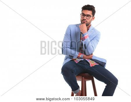 Pensive young man sitting on a chair, looking away while holding one hand to his chin.