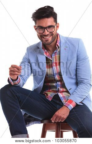 Happy young fashion man smiling to the camera while sitting on a chair.