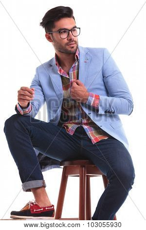 Fashion man sitting while fixing his jacket, looking away from the camera.