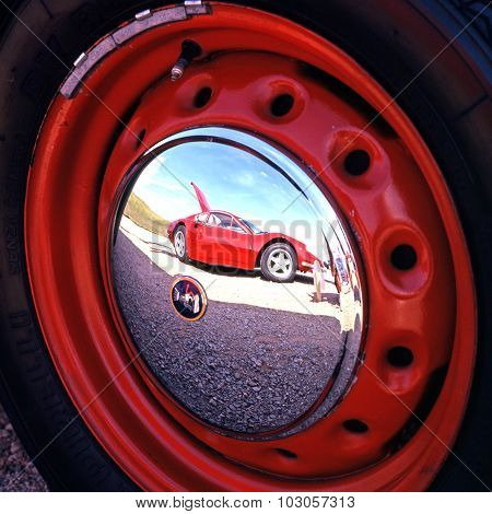 Ferrari reflected in hubcap.