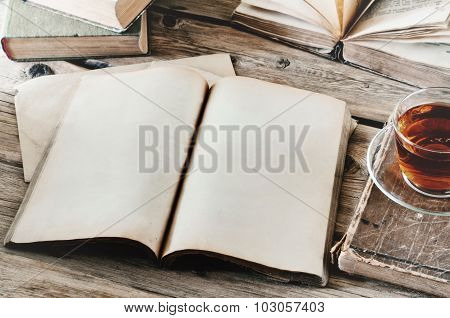 Open Book On Wooden Table With A Cup Of Tea