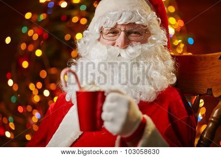 Santa Claus holding red cup with latte and looking at camera